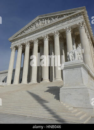 U.S. Supreme Court Building low angle.  Authority of Law statue; flag shadow on steps. - Stock Photo