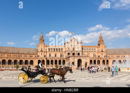Seville, Spain - April 30, 2016: A sunny day at Plaza de Espana, tourists visiting the famous square, a horse-drawn - Stock Photo