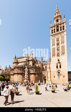 Seville, Spain - May 1, 2016: The Giralda, former minaret, today bell tower of Seville Cathedral. Tourists around - Stock Photo