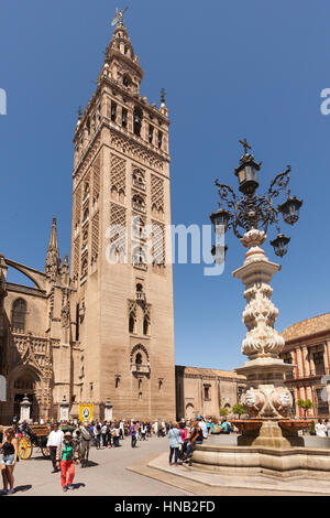 Seville, Spain - May 1, 2016: La Giralda, the bell tower of Seville Cathedral and the fountain on Plaza de Triunfo. - Stock Photo