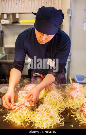 Chef Cooking Okonomiyaki,  in a restaurant of Okonomi-mura, Hiroshima, Japan - Stock Photo