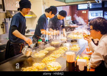 Chef Cooking Okonomiyaki,  in a restaurant of Okonomi-mura, Hiroshima, Japan - Stock Photo