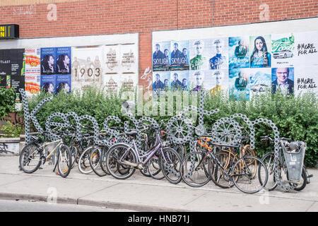 Toronto, Canada - 2 July 2016: Bike racks and Kensington neighbourhood metal sign in Toronto, Canada. - Stock Photo