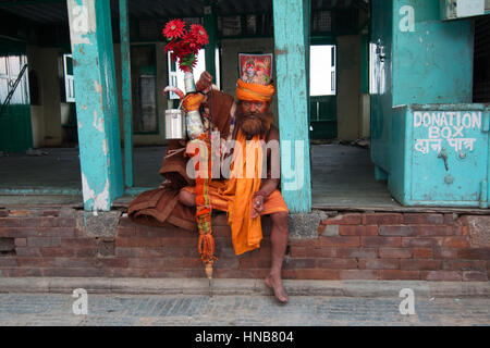 Sadhu in saffron robes at the Swayambhunath pagoda, Kathmandu, Nepal who claims to be from the holy city of Varanasi - Stock Photo