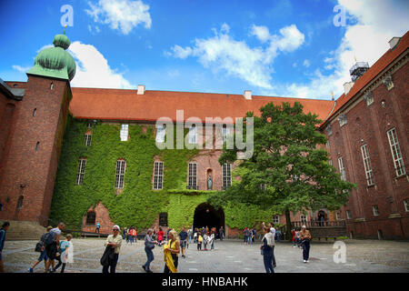 STOCKHOLM, SWEDEN - AUGUST 19, 2016: Tourists walk and visit Stockholm City Hall courtyard ( Stadshuset ), Ivy covered - Stock Photo