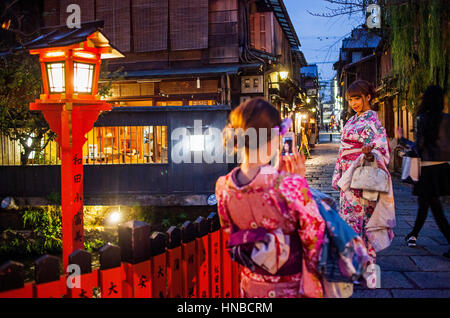 women, dressed in kimono, in Shirakawa-minami-dori, Gion district, Kyoto. Kansai, Japan. - Stock Photo