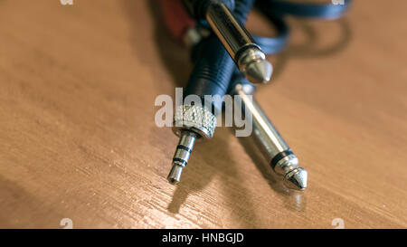 Closeup of stereo audio phone connectors plug isolated on wooden background - Stock Photo