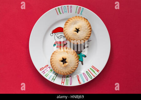 M&S Christmas all butter mince pies on festive Xmas plate as treats for Santa and Rudolph isolated on red background - Stock Photo