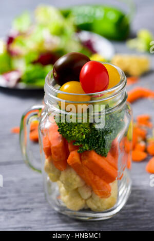 a salad with a mix of different vegetables, such as cauliflower, carrot, broccoli and cherry tomatoes of different - Stock Photo