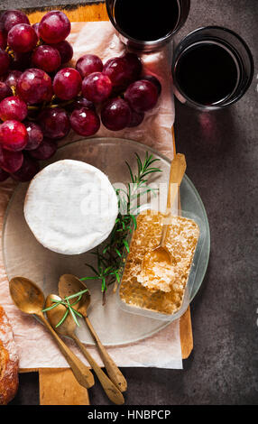 cheese board and wine. cheese, grapes, wine, honey and bread on grey stone background - Stock Photo