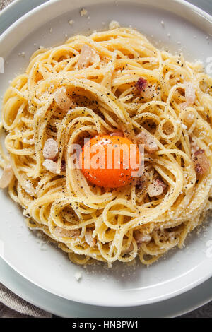 Pasta Carbonara on white plate with parmesan and yolk ...