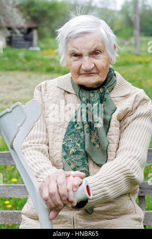Portrait of an elderly woman holding a crutch - Stock Photo