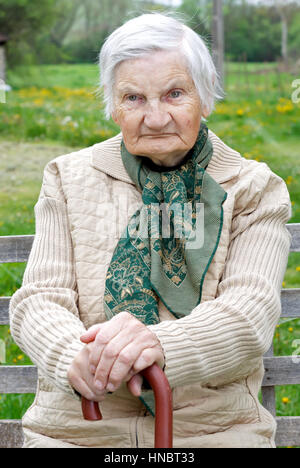 Handicapped elderly woman sitting on a the bench - Stock Photo