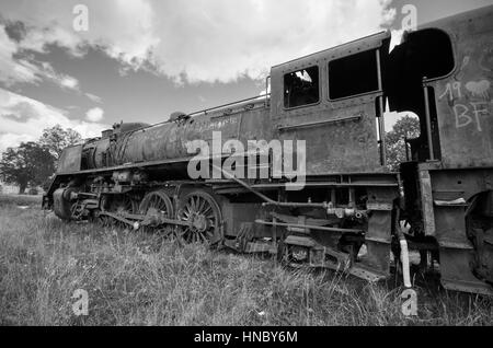Abandoned rusty steam locomotive in black and white. - Stock Photo