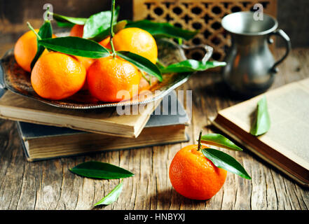 Fresh tangerines and books on a wooden table - Stock Photo