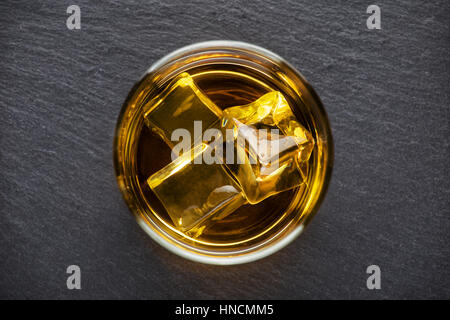 Round glass of whiskey with ice on a black background shot from above - Stock Photo