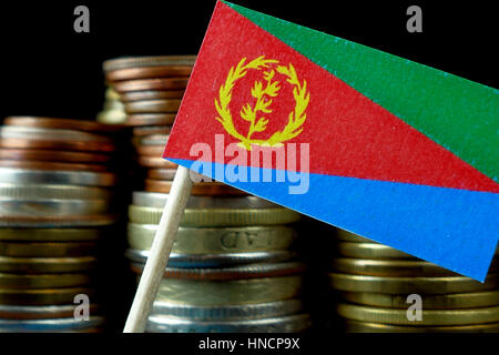 Eritrean flag waving with stack of money coins macro - Stock Photo
