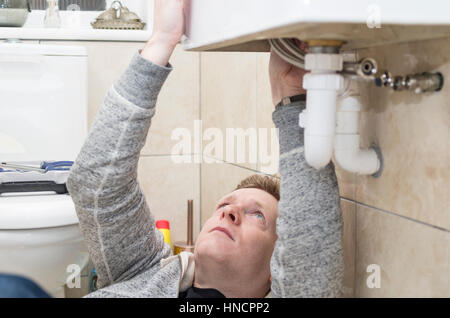 Young man attempting do it yourself diy plumbing at home under a young man attempting do it yourself diy plumbing at home under a sink fitting solutioingenieria Choice Image