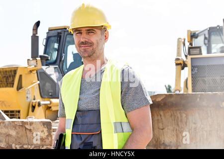 Portrait of confident supervisor standing at construction site - Stock Photo