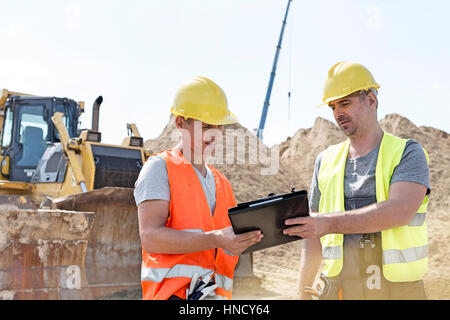 Engineers reading clipboard at construction site against clear sky - Stock Photo