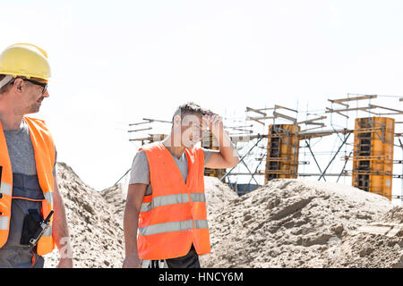Construction worker looking at tired colleague wiping sweat at site - Stock Photo