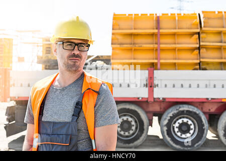 Thoughtful architect standing against truck at construction site - Stock Photo
