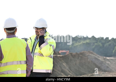 Supervisor using mobile phone while standing with colleague at construction site against clear sky - Stock Photo