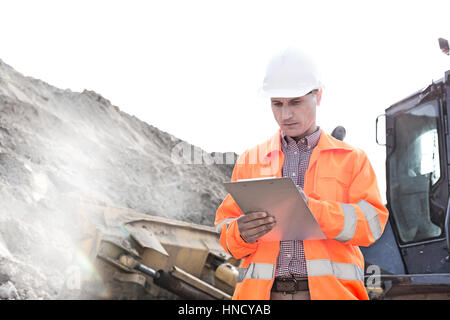 Engineer reading clipboard at construction site - Stock Photo