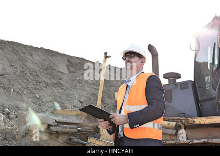 Engineer looking away while holding clipboard at construction site - Stock Photo