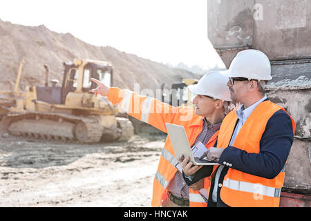 Supervisor showing something to coworker holding laptop at construction site - Stock Photo