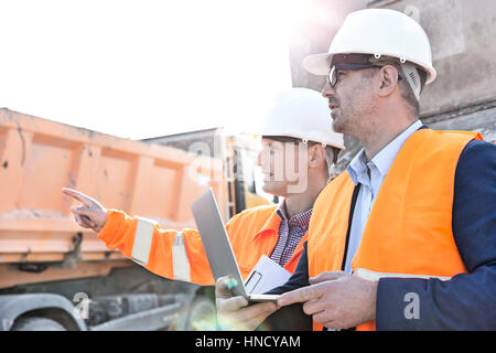 Supervisor showing something to colleague holding laptop at construction site - Stock Photo