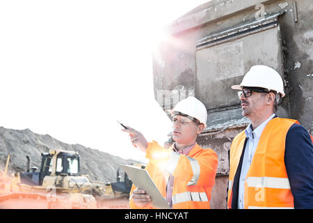 Supervisor showing something to colleague at construction site on sunny day - Stock Photo