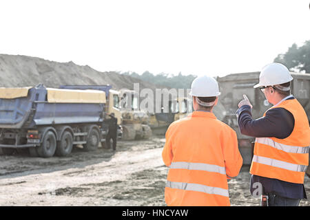 Supervisor explaining plan to colleague at construction site - Stock Photo