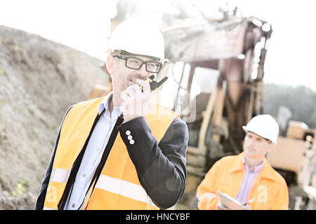 Happy engineer using walkie-talkie on construction site with colleague in background - Stock Photo
