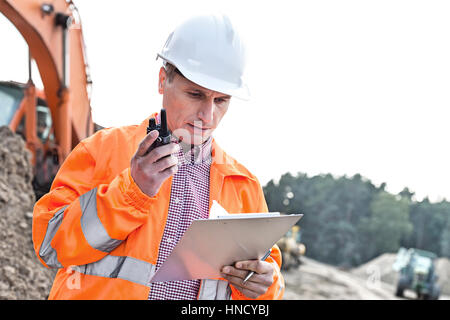 Supervisor reading clipboard while using walkie-talkie at construction site - Stock Photo