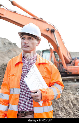 Architect looking away while holding clipboard at construction site - Stock Photo