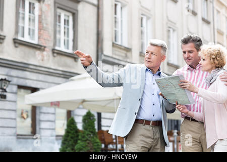 Man assisting to middle-aged couple with road map in city - Stock Photo