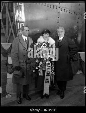Woman holding a flower bouquet, standing between two men on the dock in front of the ship at 'War Column' launching - Stock Photo