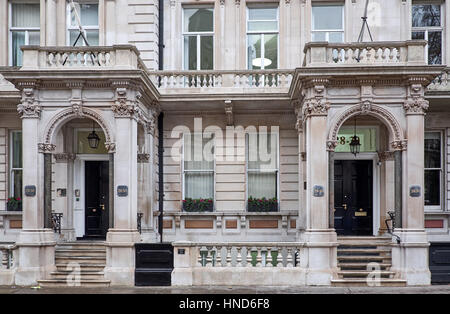 Ornamented facade in with elaborate decorations around the entrance shelter, supported on columns, of a  building - Stock Photo