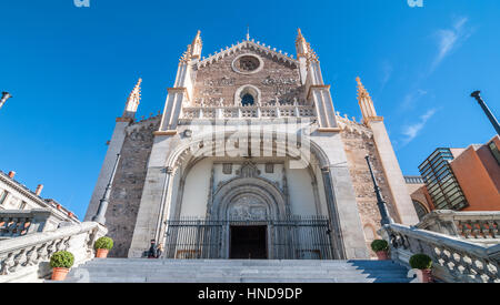 Bright, blue sky, sunshine on beautiful old stone & masonry cathedral.  Steps leading to spear-tipped wrought iron - Stock Photo