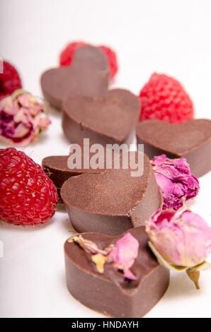 Raw chocolate hearts, roses and raspberries - Stock Photo