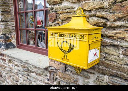 Marksburg, Germany - May 23, 2016: Retro yellow public post mailbox on a wall in Marksburg, Braubach, Germany. - Stock Photo