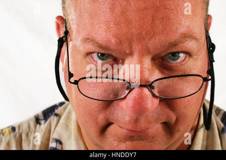 A close up of a middle aged man looking over his glasses - Stock Photo