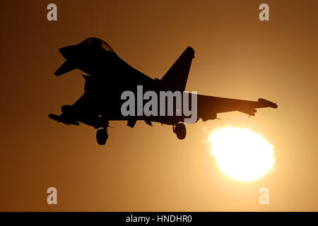 RAF Typhoon on approach to RAF Coningsby as it flies through the setting sun. - Stock Photo