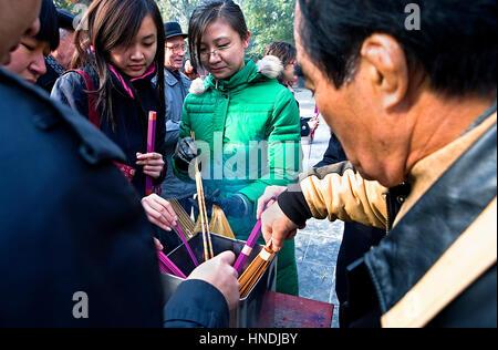 Pray, praying, offering, Believers burning incense at Yong he Gong lama temple,Beijing, China - Stock Photo