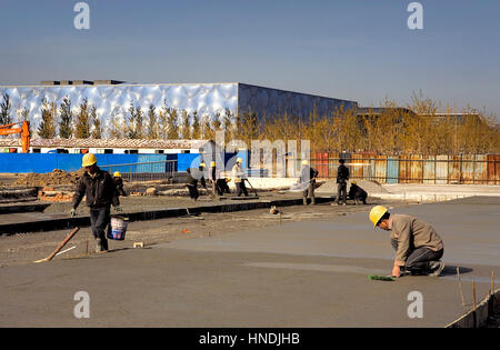 under construction, Workers in the olympic area, at background Olympic National Swimming Centre,Beijing, China - Stock Photo