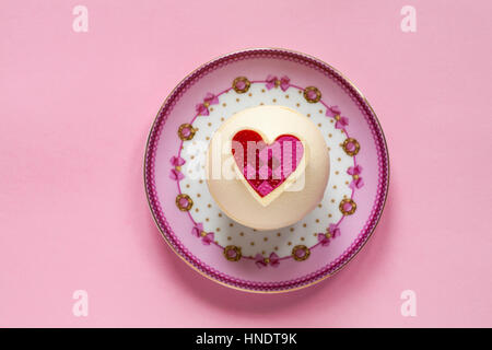 M&S Raspberry and Prosecco Spheres for dessert for Valentines Day on decorative plate isolated on pink background - Stock Photo
