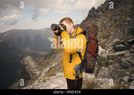 hiker photographing in mountains - Stock Photo