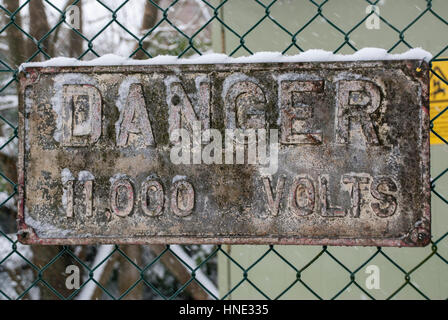 A danger voltage sign covered in snow - Stock Photo