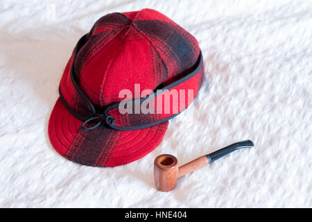 Smoking pipe used for tobacco and a red buffalo plaid hat to be worn by a groom on his wedding day. - Stock Photo